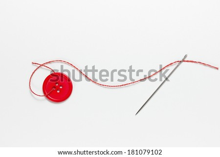 A threaded needle and red button - stock photo