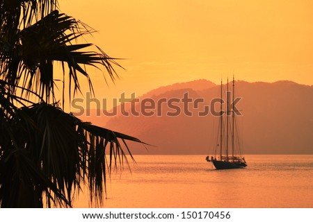 A three-masted sailing vessel in a calm bay in the evening - stock photo