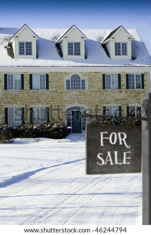 A three stroy house is for sale with a wooden sign out front. - stock photo
