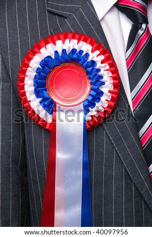 A three tiered rosette on a grey pinstripe suit, blank centre to add you own text. Suitable uses could  include votes, award and political themes. - stock photo