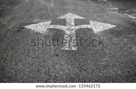 A three way arrow symbol on a black asphalt road surface. - stock photo