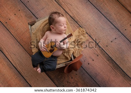 A three week old baby boy wearing jeans and playing a tiny acoustic guitar. He is lying in a wooden crate lined with burlap. Shot in the studio on a rustic, wood background. - stock photo