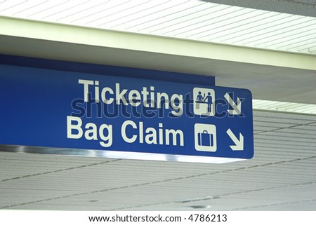 A ticketing and bag claim sign inside an airport.