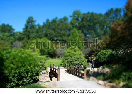 A Tilt Shift image of a man near a bridge - stock photo