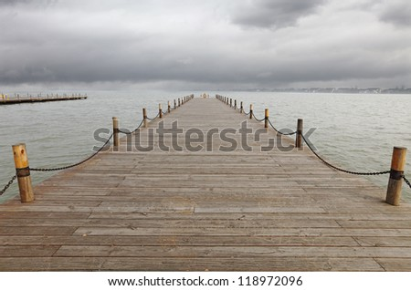 A timber jetty pier on a lake stretching into the horizon of a stormy cloudy skyline. - stock photo