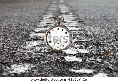A timeless vintage watch resting on a dividing line in a deserted road leading into the horizon for the concept of Crossing the Deadline. - stock photo