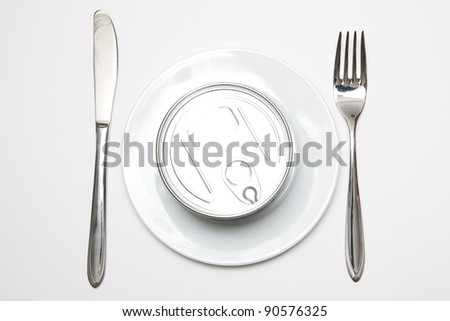 A tin can on a plate with a knife and fork