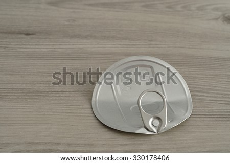 A tin lid isolated on a wooden table  - stock photo