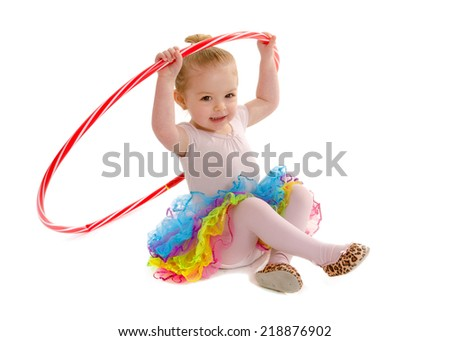 A Tiny Dancer in preschool having fun with hula hoop and colorful tutu - stock photo