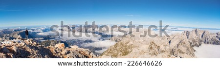 A tiny man enjoying panoramic view from the top of the Triglav mountain ( Slovenia's highest peak) - stock photo