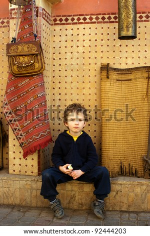 A tired and exhausted boy sits on the street of Marrakesh