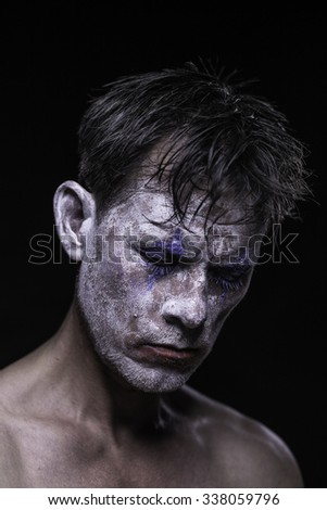 A tired and sad clown with crumbling, worn-out make up. - stock photo