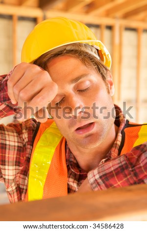 A tired construction worker wiped his head - stock photo