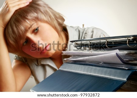 A tired young woman sitting at the desk, having a lot of paperwork to do, focus on a pile of documents