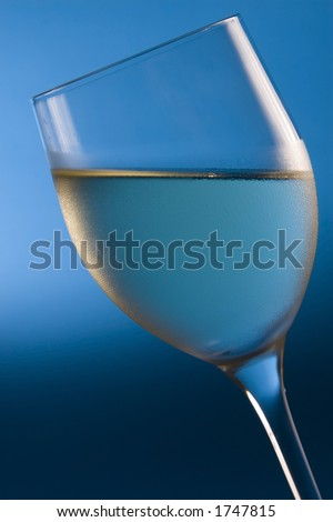 A titled wine glass filled with white wine is shot against a blue background.  Condensation on the glass suggests the chilled tempature of the wine. - stock photo