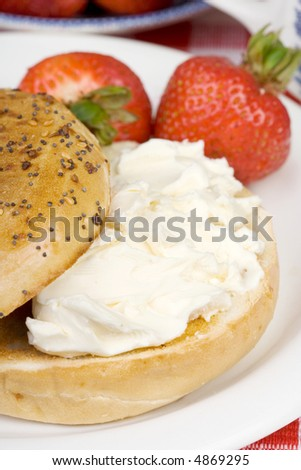 A toasted bagel covered with cream cheese. Fresh strawberries on the side. Shallow dof. - stock photo