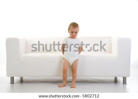 A toddler/child stands in front of a clean, white sofa, putting his hands behind his back. - stock photo
