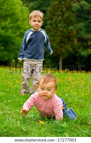 A toddler girl crawling on the grass in a park with elder brother watching.