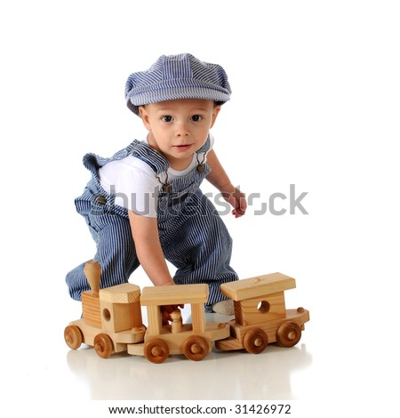 A toddler in striped denim overalls and engineer's cap playing with a wooden train.  Isolated on white. - stock photo