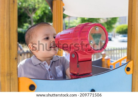 A toddler looking through a toy telescope in a playground - stock photo