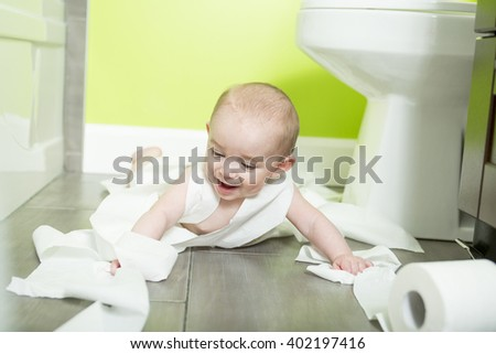 A Toddler ripping up toilet paper in bathroom