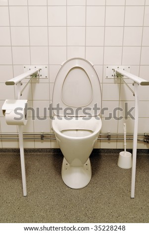 A toilet with aids for people with disabilities. - stock photo