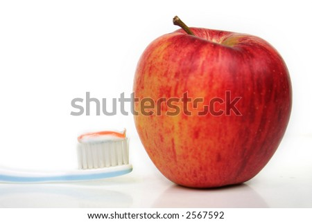 a toothbrush with toothpaste and an apple in front of white background - stock photo