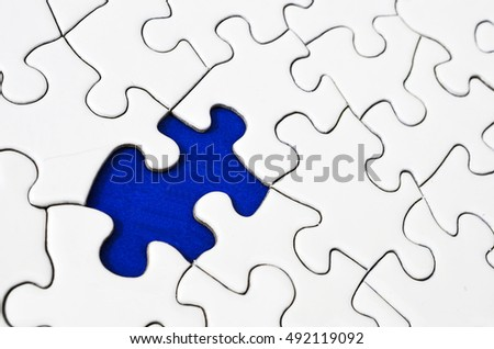 A top view image of a white jigsaw puzzle with a missing puzzle piece.