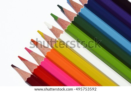 A top view image of multicolored pencil crayons on a white background.