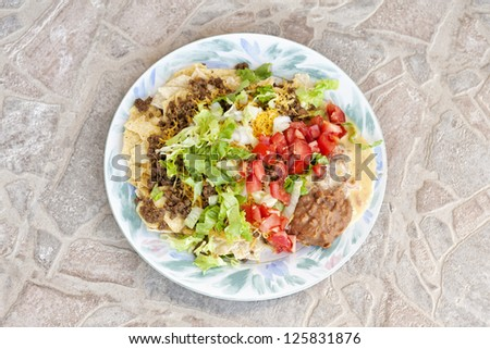 A top view of a plate filled with Mexican beef taco salad topped with lettuce, tomato, onion and cheese, horizontal with copy space - stock photo