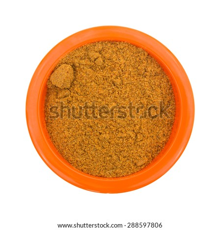A top view of a portion of grainy cajun seasoning in a small orange bowl.