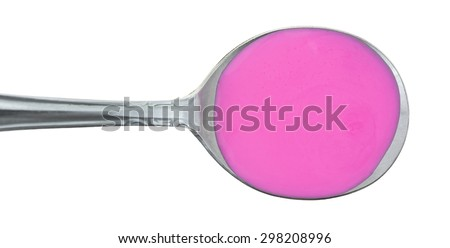 A top view of a silver spoonful of pink medicine for stomach relief. - stock photo