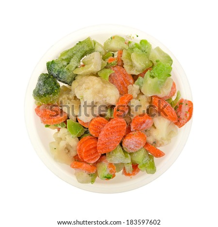 A top view of a variety of prepared frozen vegetables in a bowl on white.  - stock photo