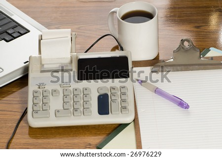 A top view of an office desk with focus on the calculator - stock photo