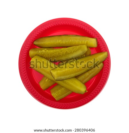 A top view of bread and butter pickle sticks on a red plate and white background. - stock photo