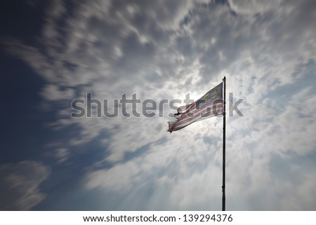 A torn and tattered Malaysian flag flying on a flag post against a dramatic cloudy sky.  - stock photo
