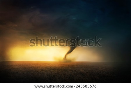 A tornado in a field at sunset. - stock photo