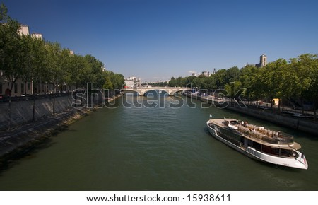 A tour boat cruising on the river Seine in Paris. - stock photo