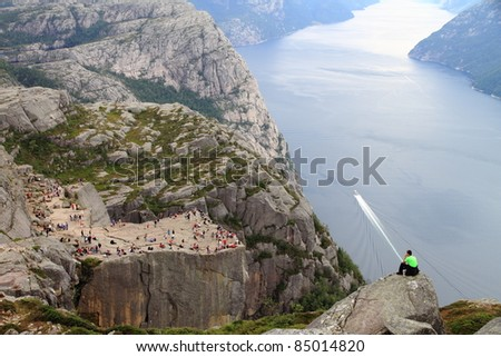 A tourist amazed observing Pulpit Rock at Lysefjorden in Norway. A well known tourist attraction towering 604 meters over sea level - stock photo