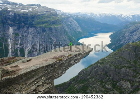 A tourist on a famous norwegian Mountain Vibrant Landscape Trolltunga Odda Fjord Norge Hiking Trail Waterfall The Troll Tongue Norge Scandinavia Nature Travel  Oslo Fjord  - stock photo