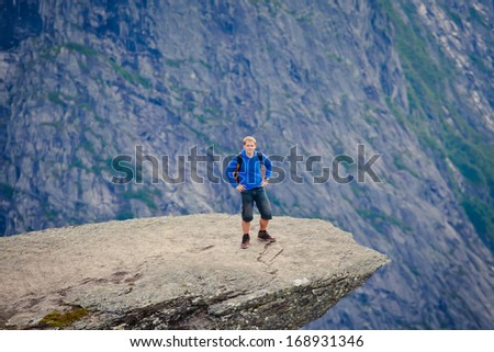 A tourist on a famous norwegian rock looking all epic - stock photo