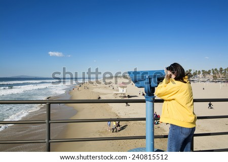 A tourist on the Huntington Beach pier watches surfers through coin operated binoculars during a bright, sunny day. T - stock photo
