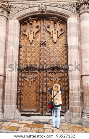 A tourist photographs the massive, ornate door to the cathedral in San Miguel de Allende, Mexico - stock photo