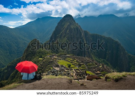 A tourist under the shade of a red umbrella looking at Machu Picchu.  There is also a brown llama admiring the view as well. - stock photo