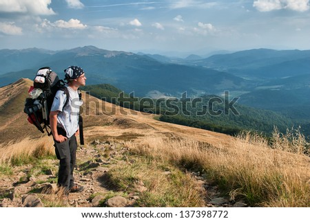 A tourist with backpack in the mountains