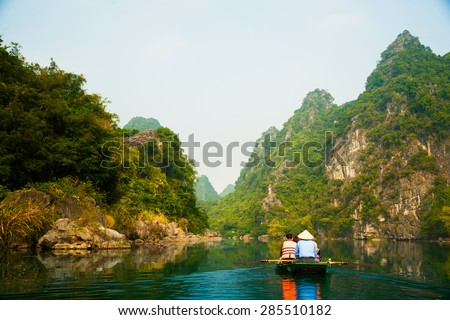A touristic boat moves through a river between beautiful mountains of Trang An Grottoes, one of the main destinations in Ninh Binh Province, Vietnam