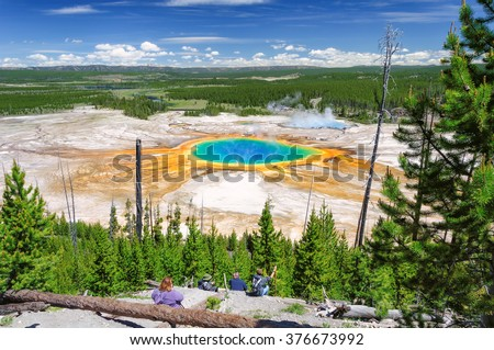 A tourists looking down on Grand Prismatic Spring in Yellowstone National Park, the largest hot spring in the United States - stock photo