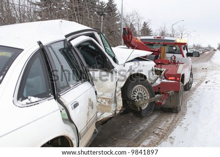 A tow truck hauls away a car from an accident scene. - stock photo