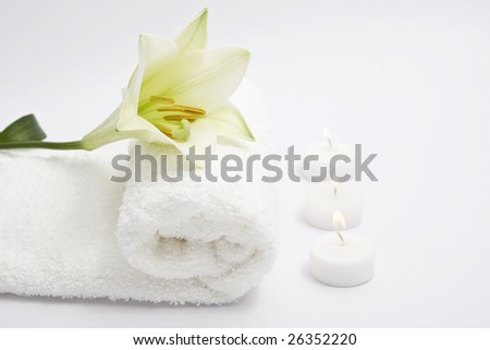 A towel, a flower and three candles on white background. Copy space. - stock photo