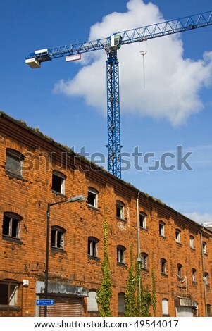 A tower crane on a construction site dominates derelict warehousing - stock photo